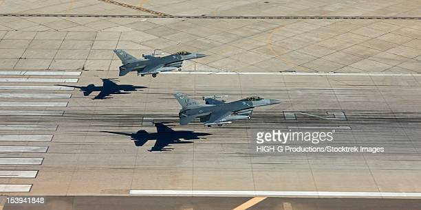 Two F-16's from the 56th Fighter Wing at Luke Air Force Base, Arizona, land in formation on runway 21.