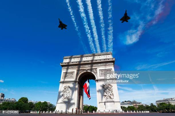 Two F22 of the US Air Force fly over the Arc de Triomphe on the Champs Elysees Avenue in Paris on July 14 during the Bastille Day military parade...