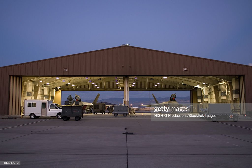 Two F-22 Raptors sit in their hangars while maintenance crews work on them between sorties at Holloman Air Force Base, New Mexico. : Stock Photo