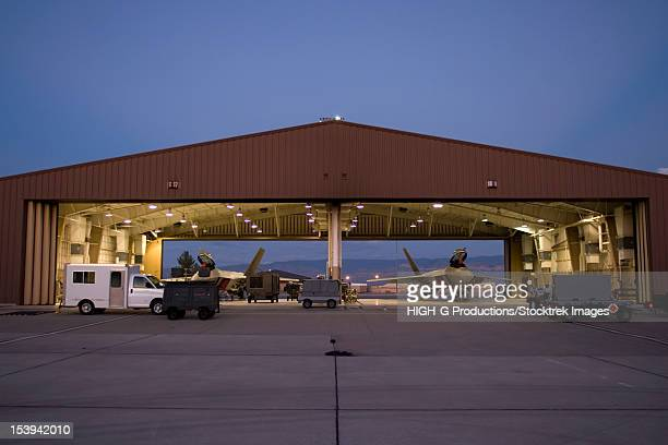 Two F-22 Raptors sit in their hangars while maintenance crews work on them between sorties at Holloman Air Force Base, New Mexico.
