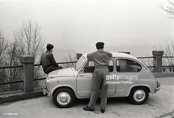 Two factory workers of FIAT Group look at Turin from above at the end of their workshifts after parking of their FIAT Cinquecento Thanks to the...