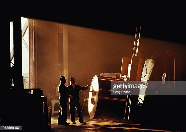 two factory workers standing by large roll of sheet aluminium - aluhut stock-fotos und bilder