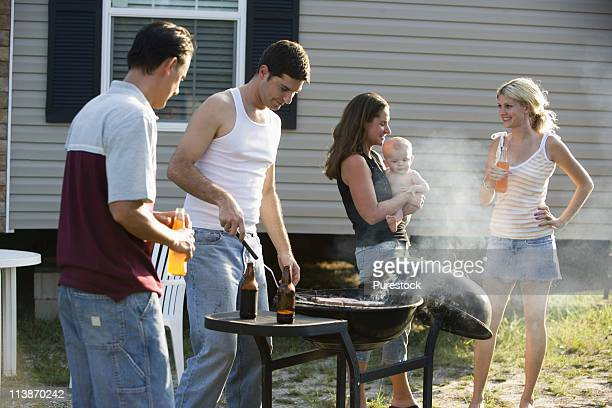 Two families enjoying a cookout in front of a trailer home