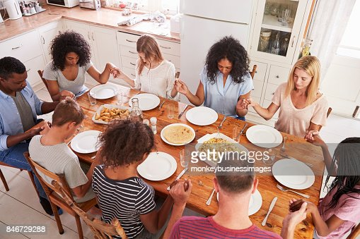 Two Families Saying Grace Before Eating Meal Together Stock