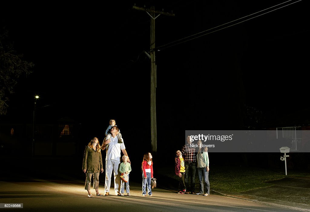 Two families standing looking up at night sky : Stock Photo