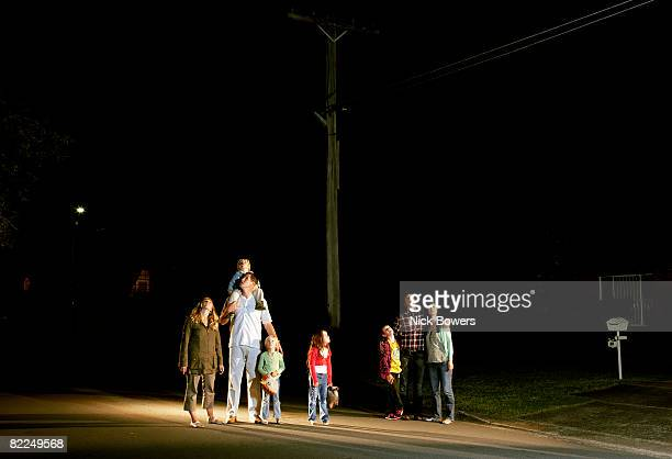 Two families standing looking up at night sky