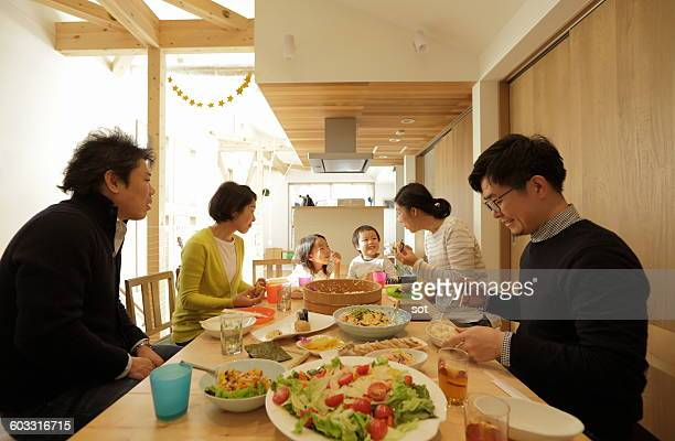 Two family enjoying meal at home party
