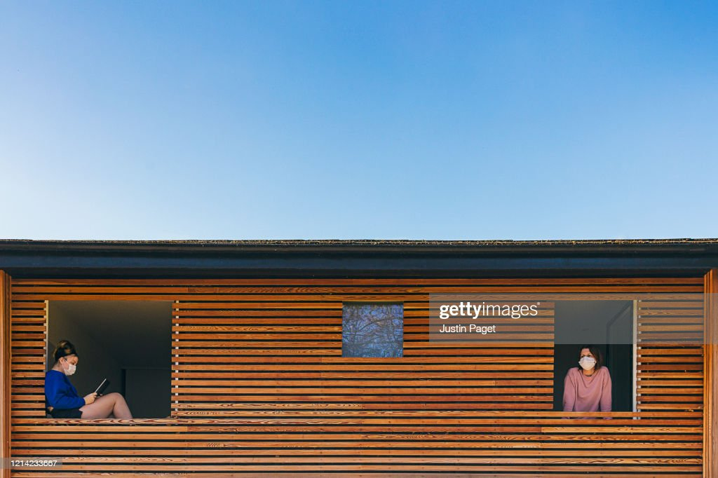 Two family members in self isolation in different rooms : Stock Photo