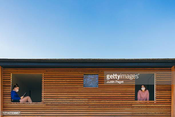 two family members in self isolation in different rooms - social distancing stock pictures, royalty-free photos & images