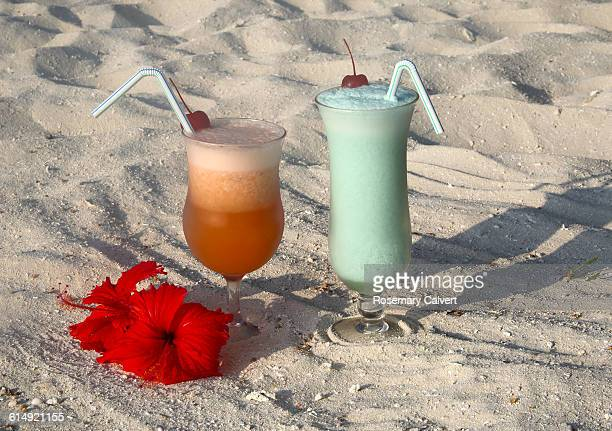 Two fancy cocktails on coral beach ready to drink