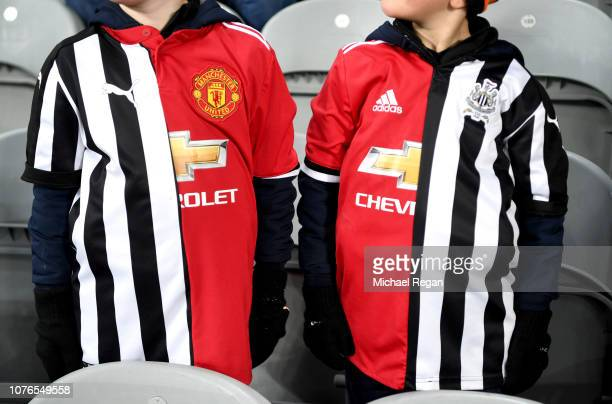 Two fans are seen wearing half and half kits prior to the Premier League match between Newcastle United and Manchester United at St James Park on...
