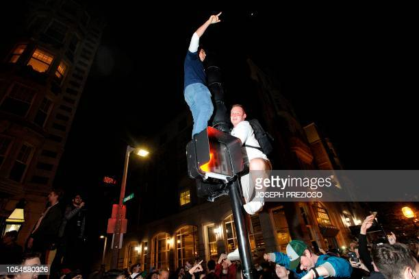 Two fans climb at cross walk light as fans celebrate the Red Sox World Series victory over the LA Dodgers at Boston Common in Boston Massachusetts...