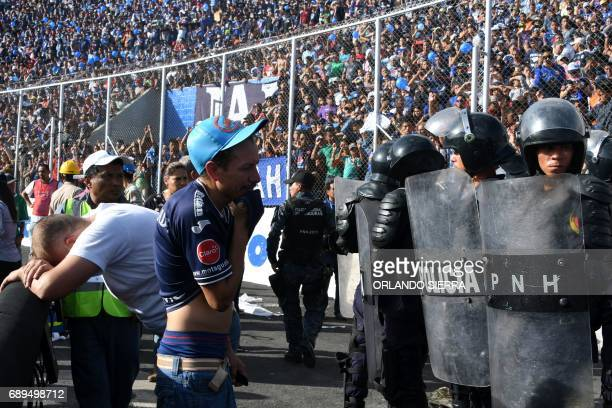 Two fans cry after two supporters of Honduran team Motagua died in a stampede at the National Stadium in Tegucigalpa on May 28 2017 At least two...