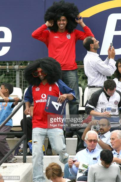 Two fans dressed in large afro wigs enjoy the match in the stands