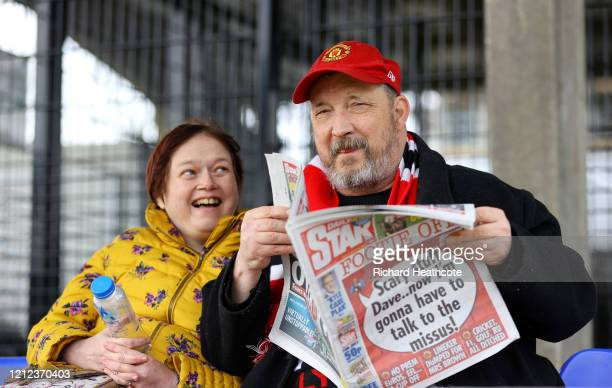 Two fans enjoy the pre match atmosphere by reading a newspaper prior to the Vanarama National League match between Maidenhead United and Stockport...