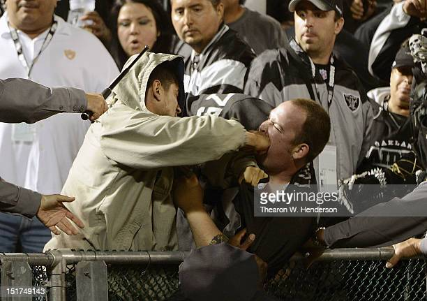Two fans fight during the season opener of an NFL football game between the San Diego Chargers and Oakland Raiders at Oakland-Alameda County Coliseum...