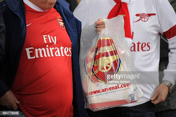 Two fans of Arsenal with a bag with an Arsenal logo from the club shop
