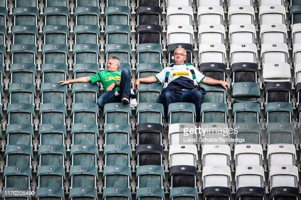 Two fans of Mönchengladbach relax on the stands after the win of the Bundesliga match between Borussia Mönchengladbach and Fortuna Düsseldorf at...