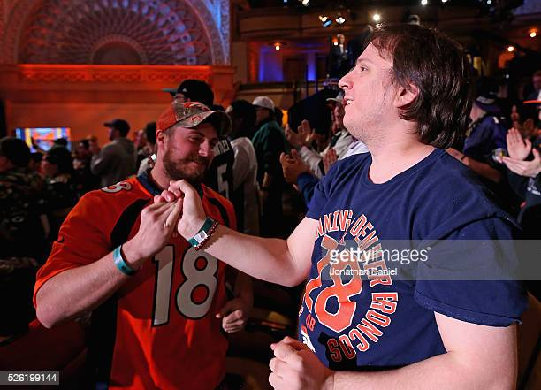 Two fans of the Denver Broncos celebrate their teams' pick during the 2016 NFL Draft at the Auditorium Theater on April 28 2016 in Chicago Illinois