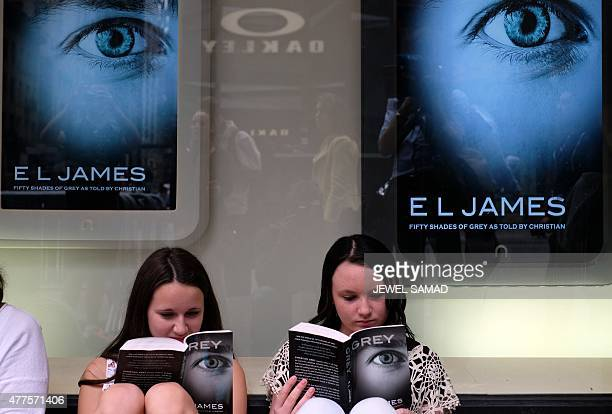 Two fans read their copies of EL James's new book 'Grey Fifty Shades of Grey as Told by Christian' as they wait outside the Barnes and Noble store on...