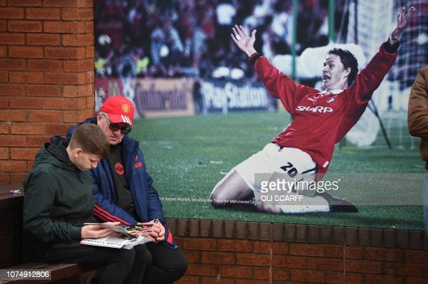 Two fans sit on a bench next to a poster of Manchester United's Norwegian striker and now caretaker manager Ole Gunnar Solskjaer celebrating scoring...