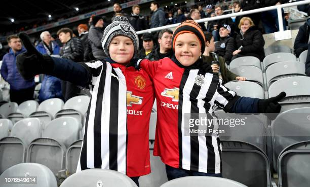 Two fans that are seen wearing half and half kits pose for a photo prior to the Premier League match between Newcastle United and Manchester United...