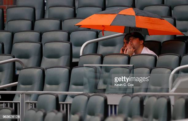 Two fans wait out a weather delay prior to the game between the Atlanta Braves and the New York Mets at SunTrust Park on May 29 2018 in Atlanta...