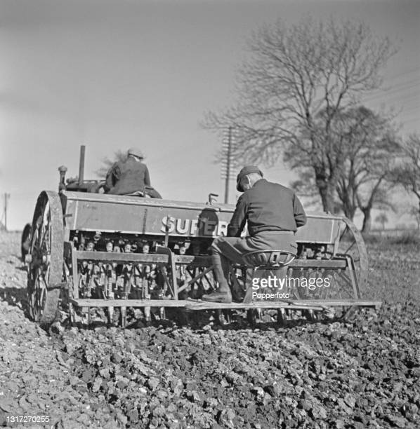 Two farm workers operate a tractor and seed drill to sow seed in a recently ploughed field at Ernest Smith's arable farm near Ware in Hertfordshire,...
