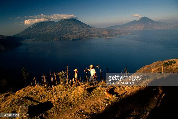 Two farmers and a dog near Lake Atitlan with the Atitlan volcanoes in the background Toliman and San Pedro Guatemala