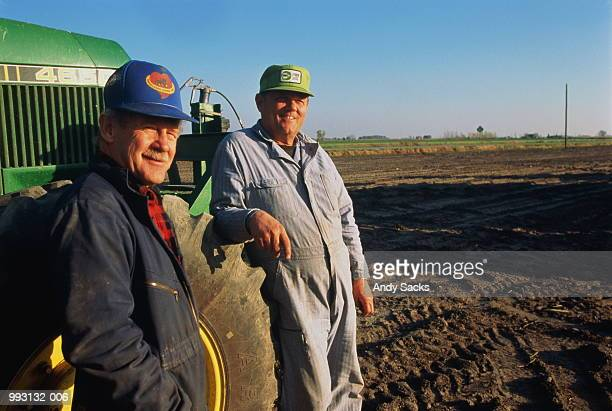 Two farmers standing by tractor in field