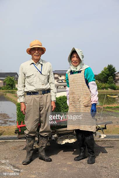 Two Farmers Standing in front of Rice Paddy in Spring