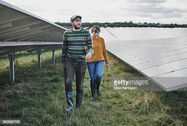 Two farmers walking through solar farm