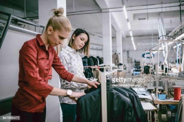 two fashion designers checking the quality of their product - fábrica têxtil imagens e fotografias de stock