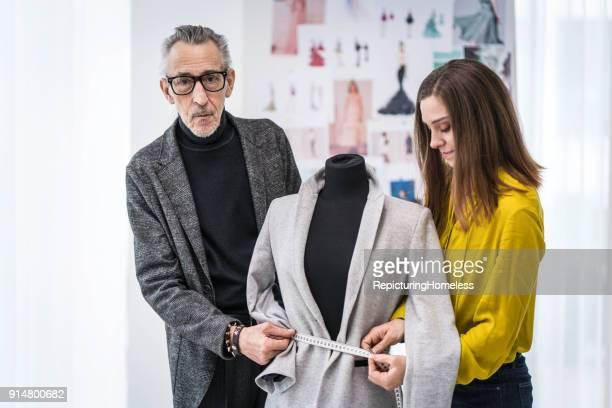 Zwei Mode-Designer vermessen Stoff an einer Ankleidepuppe