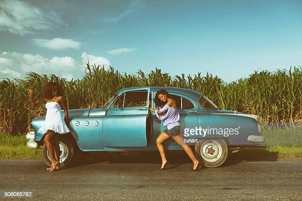 Zwei Mode-Modelle und alte, alte, defekte Auto in Kuba