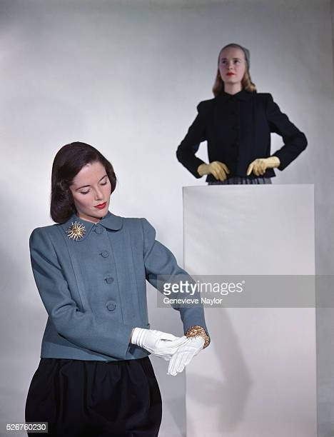Two fashion models model new fall coats designed by Henry Brendel, gloves designed by Van Raalte, and costume jewelry designed by Van Cleef & Arpels.