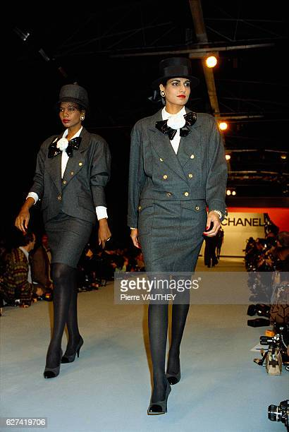 Two fashion models walk in the latest readytowear women's line by French fashion house Chanel at the 19871988 FallWinter fashion show in Paris The...
