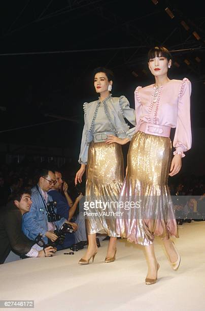 Two fashion models wear readytowear blazers and shiny skirts by Italian fashion designer Valentino They are modeling the outfits during his...