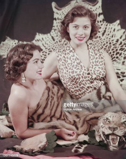 Two fashion models wearing leopard print and tiger print outfits, circa 1955.