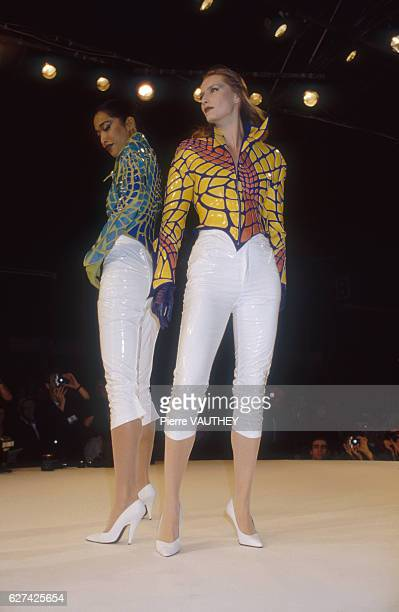 Two fashion models wearing matching readytowear jackets and tight capri pants by German fashion designer Thierry Mugler They are modeling the outfits...