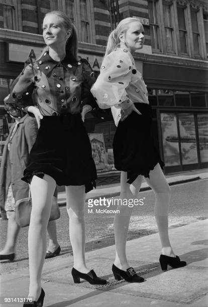 Two fashion models wearing puffy sleeve see through blouses and black skirt UK 10th September 1968