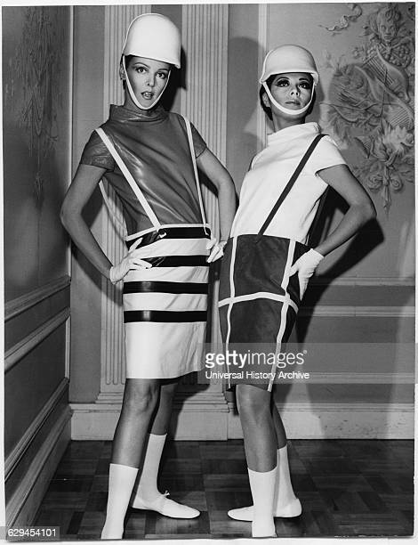 Two Fashion Models Wearing Sleek Interpretations of Andre Courreges' Suspender Outfits Featuring Barrel Skirts with ButtonAttached Suspenders and...
