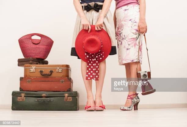 two fashionable dressed women posing at the suitcases in retro style - multi colored hat stock pictures, royalty-free photos & images