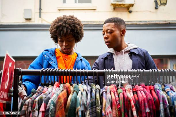 two fashionable friends looking for clothes at a market - shop stock pictures, royalty-free photos & images