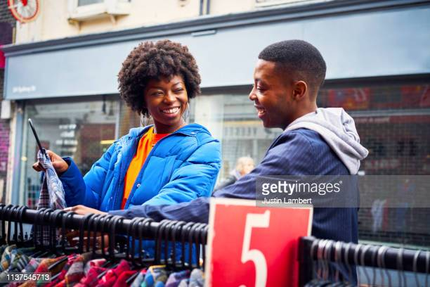 two fashionable friends looking for clothes at a market smiling - for sale frase em inglês imagens e fotografias de stock
