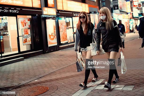 Two fashionable girls in knee-high socks walk at night through the shopping and entertainment district of Shibuya in Tokyo.