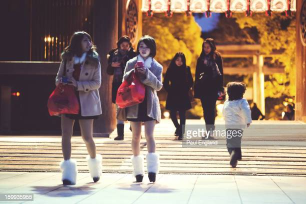 Two fashionable girls wearing leg warmers show up to pay their respects at Meiji Shrine on New Years' Eve.