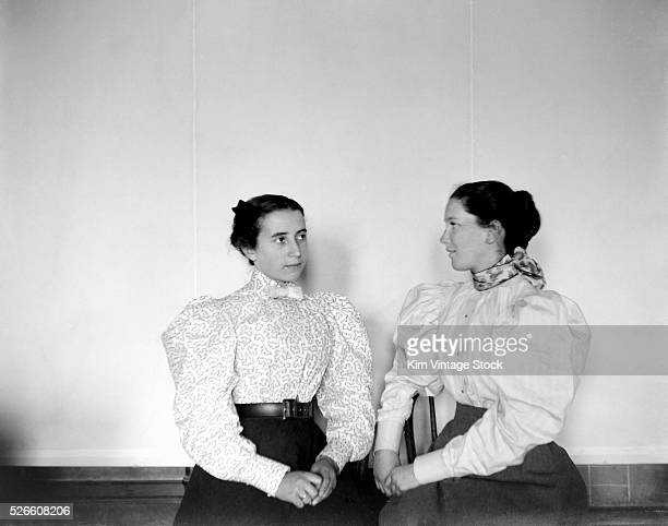 Two fashionable young women pose together ca 1900