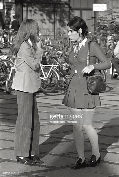 Two fashionably dressed young women in the centre of Copenhagen The liberation movement has spread the way of wearing long trousers and short skirts...