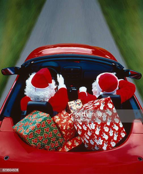 Two Father Christmas driving a cabriolet